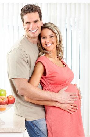 Glimlachende mooie zwangere vrouw en man bij keuken  Stockfoto