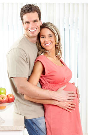 mom and dad: Smiling beautiful pregnant woman and man  at kitchen