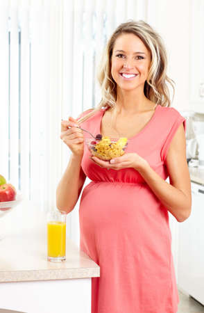 woman on couch: Smiling beautiful pregnant woman eating cereals at kitchen