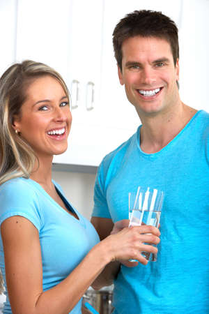 girl drinking water: Young beautiful smiling couple at home