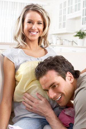 bump: Smiling beautiful pregnant woman and man  at home