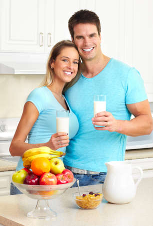 Jonge mooie lachende paar consumptie melk thuis