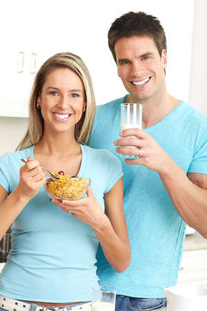 Young beautiful smiling couple drinking milk and eating cereals photo