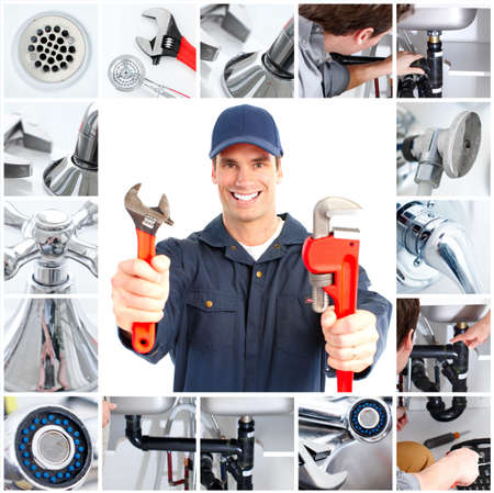 sink drain: Smiling handsome plumber with an adjustable wrench