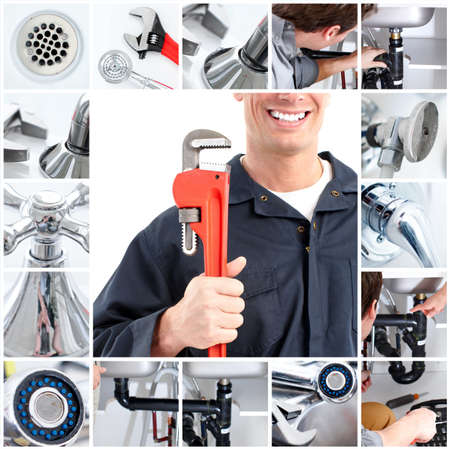 plumbing: Smiling handsome plumber with an adjustable wrench  Stock Photo