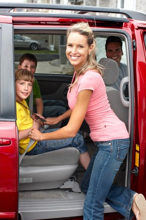 Smiling happy family and a family car