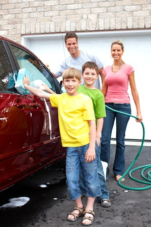 Smiling happy family washing the family car