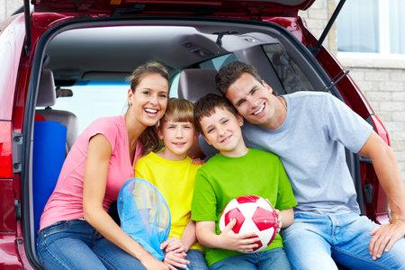 Familia feliz sonriente y un coche familiar