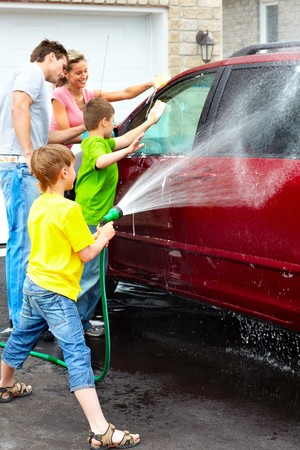 Smiling happy family washing the family car photo