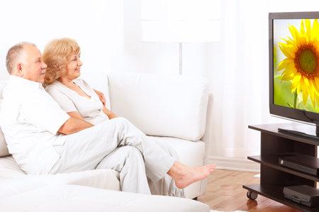 幸せな家庭でテレビを見ている年配のカップルの笑みを浮かべて 写真素材