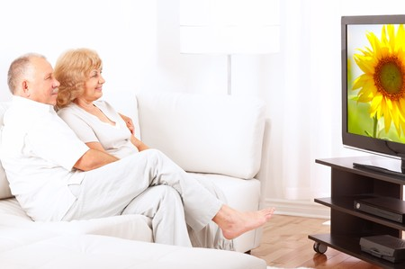 Happy smiling senior couple watching TV at home