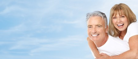 Happy smiling elderly seniors couple under blue sky