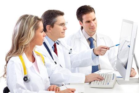 doctores: Sonrientes m�dicos trabajando con un ordenador. Aislados sobre fondo blanco