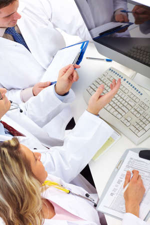 Smiling medical doctors working with a computer.