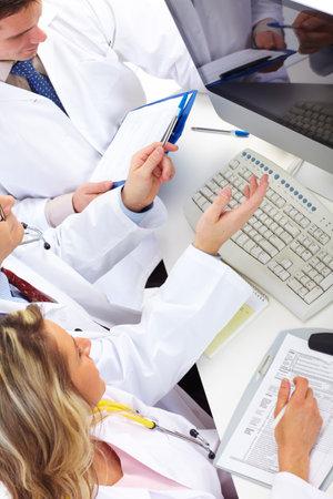 Office uniforms: Sonrientes m�dicos trabajando con un ordenador.