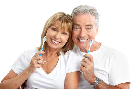 brush teeth: Happy seniors couple with toothbrushes. Healthy teeth. Isolated over white background  Stock Photo
