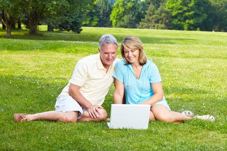 Happy elderly seniors couple with laptop in park  photo