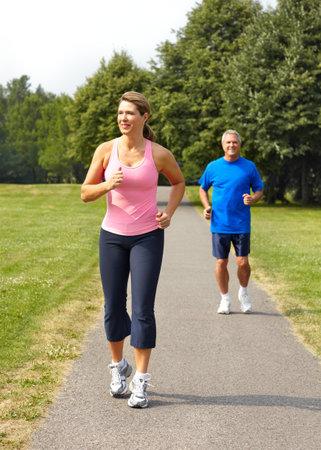 Happy elderly seniors couple jogging in park