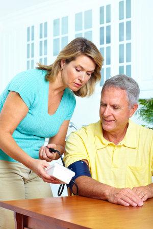 Seniors couple at home measuring blood pressure. Home monitoring 免版税图像