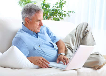 Smiling elderly senior man with laptop at home  photo