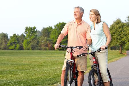 montando bicicleta: Pareja de personas mayores de edad feliz ciclismo en Parque