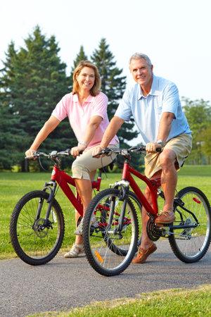 Happy elderly seniors couple biking in park  photo