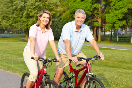 Happy elderly seniors couple biking in park  Imagens