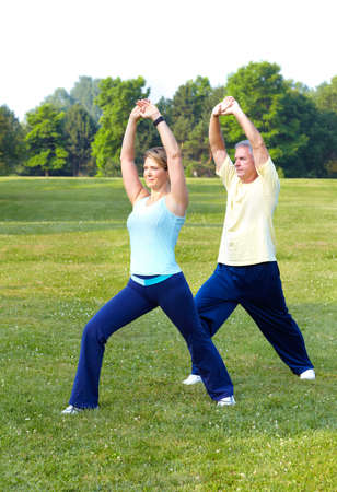 Happy elderly seniors couple working out in park Stock Photo - 7362355