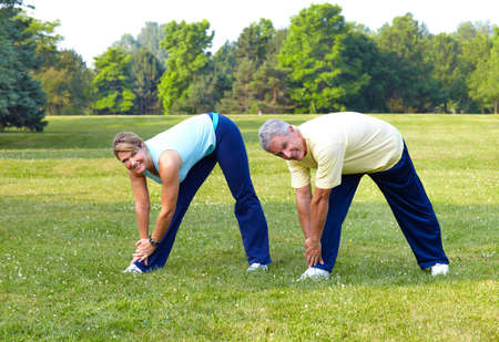 sports and recreation: Happy elderly seniors couple working out in park