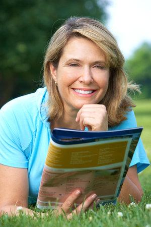 leggere rivista: Felice donna anziana sorridente, leggendo una rivista