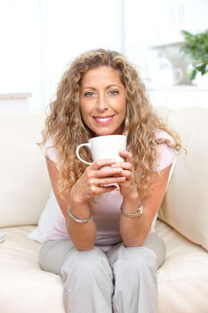 Smiling elderly woman with a cup   photo