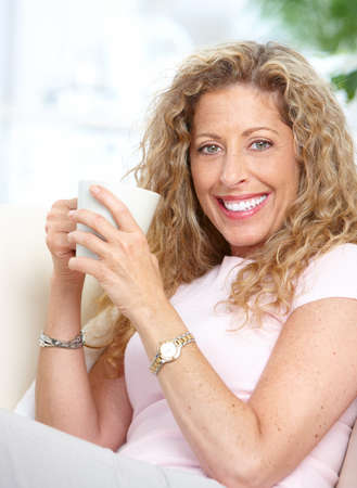 Smiling mature woman with a cup   photo