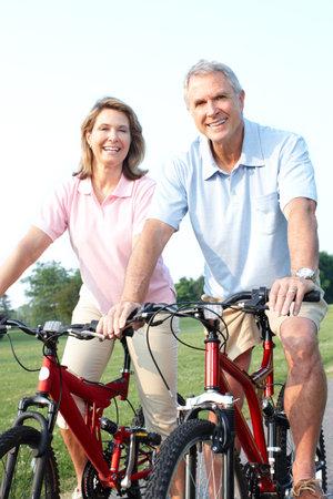 公園で自転車に乗ること幸せな高齢者高齢者のカップル