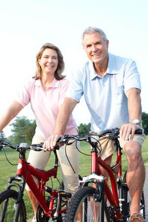 adult couple: Happy elderly seniors couple biking in park  Stock Photo