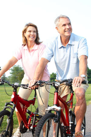 Happy elderly seniors couple biking in park Stock Photo - 7365021