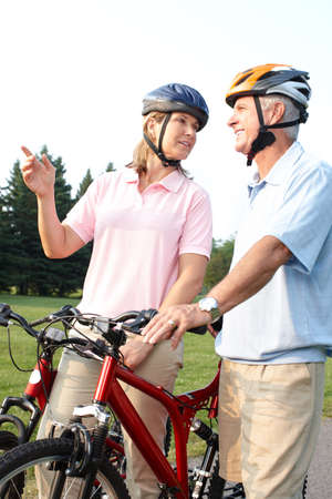 Happy elderly seniors couple biking in park Stock Photo - 7365030