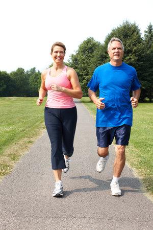Happy elderly seniors couple jogging in park  photo