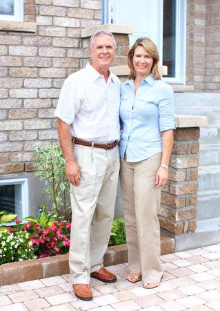 real estate house: Smiling happy elderly seniors couple near the home