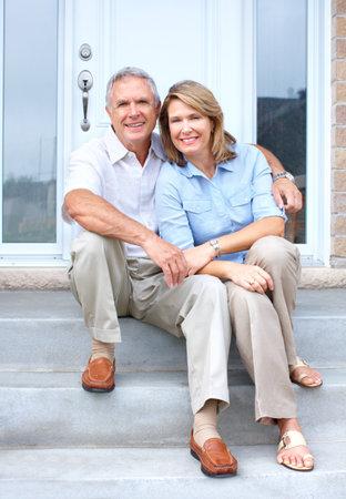 Smiling happy elderly seniors couple near the home  photo