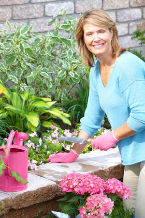 Smiling happy  woman gardening near the home  photo