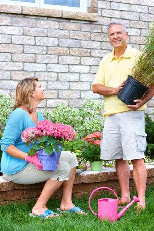 Smiling happy elderly seniors couple gardening near the home Stock Photo - 7365066