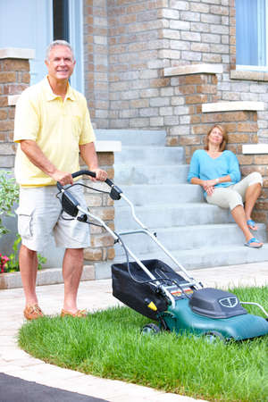 Smiling happy elderly senior man with lawnmover  photo
