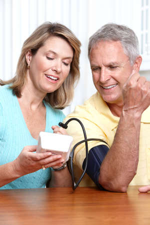 blood pressure: Seniors couple at home measuring blood pressure. Home monitoring  Stock Photo