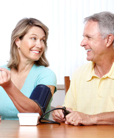 Seniors couple at home measuring blood pressure. Home monitoring  photo