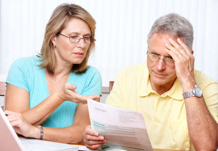 prendre sa retraite: Couple senior travaillant avec un ordinateur portable � la maison  Banque d'images