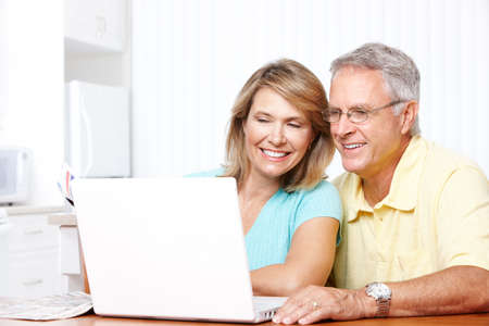 technology: Seniors couple  working with laptop at home Stock Photo