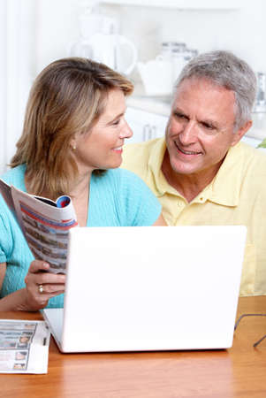 Seniors couple  working with laptop at home photo