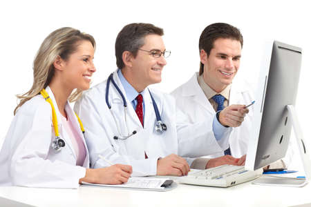 Smiling medical doctors working with a computer. Isolated over white background  photo