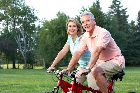 Happy elderly seniors couple biking in park  Stock Photo