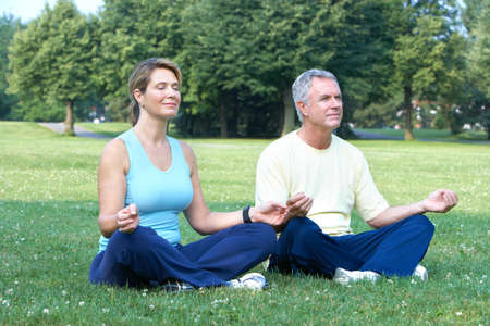 Happy elderly seniors couple doing yoga in park  photo
